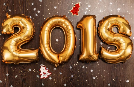 Bright gold balloons figures 2018, New Year Balloons with glitter stars on dark wood table background. Christmas and new year celebration