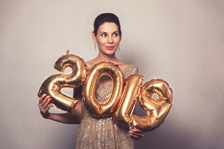 Happy New Year. Beautiful Woman with Balloons Celebrating new years Eve Party. Smiling Girl in Bright Shiny Dress with 2019 Gold Number Balloons Fun At Celebration
