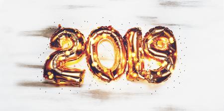 Bright metallic gold balloons figures 2019, Christmas, New Year Balloon with glitter stars on dark wood table background Stock Photo