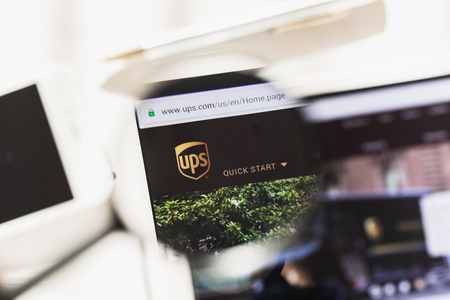 Los Angeles, California, USA - 27 February 2019: United Parcel Service official website homepage under magnifying glass. Concept United Parcel Service logo visible on smartphone, tablet screen,