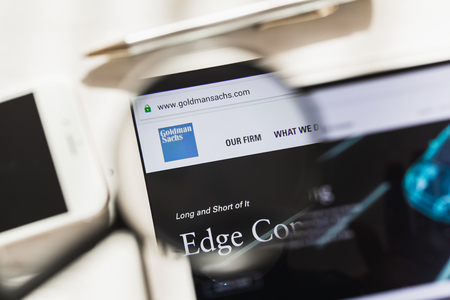 New York, USA - 4 March 2019: Goldman Sachs Group official website homepage under magnifying glass. Goldman Sachs Group logo visible on smartphone, tablet screen