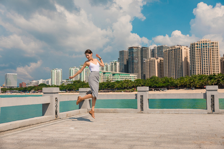 Cheerful and beautiful girl having fun on vacation, jumping on the pier on background of city. In China, Hainan city of Sanya. View of island in bay. Town Sanya is popular tourist destination in China