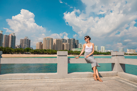 Cheerful and beautiful girl resting fun in vacation, on the pier on background of city. In China, Hainan city of Sanya. Town Sanya is popular tourist destination in China. View of island in bay