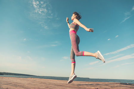 Sporty young girl in the morning on pier in jump, practicing yoga. Woman do gymnastics outdoors. Health and Yoga Concept. Female lifestyle meditation for fitness lifestyle the nature background Stock Photo