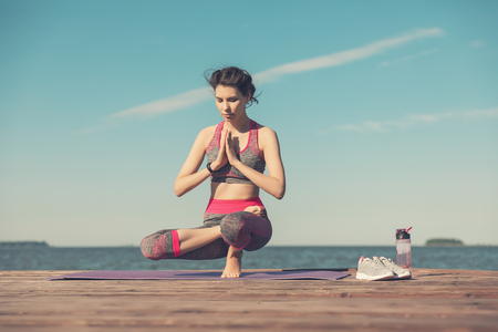 Sporty young girl in the morning on the pier on seashore, practicing yoga. Woman do gymnastics outdoors. Health and Yoga Concept. Female meditation for fitness lifestyle the nature background Stock Photo
