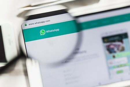 San Francisco, California, USA - 14 March 2019: WhatsApp Messenger, social official website homepage under magnifying glass. Concept WhatsApp, social network logo visible on smartphone, tablet screen
