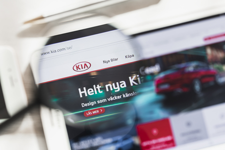 Seoul, South Korea - 14 March 2019: Kia Motors Corporation, car, official website homepage under magnifying glass. Concept KIA Motor Company, Car logo visible on smartphone, tablet screen Editorial