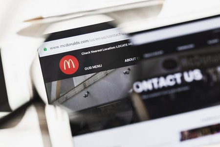 San Bernardino, California, USA - March 16, 2019: McDonalds Corporation, McDonald official website homepage under magnifying glass. Concept McDonald logo visible on smartphone, tablet screen