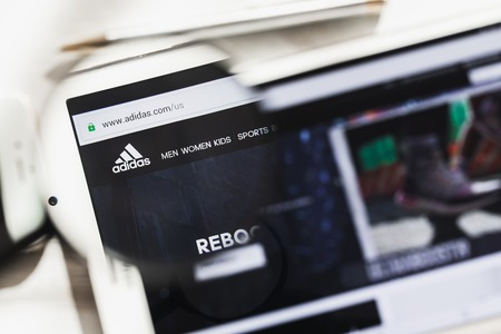 Herzogenaurach, Germany - March 16, 2019: Adidas AG, multinational corporation official website homepage under magnifying glass. Concept Adidas logo visible on smartphone, tablet screen