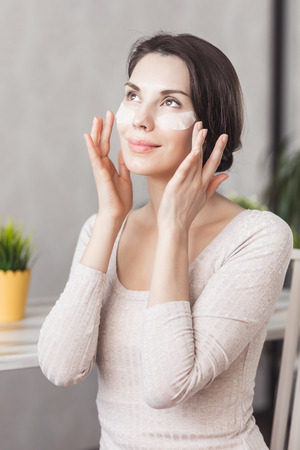 Makeup remove skin care. Closeup woman holding cotton swab and makeup remover liquid cosmetic in hands. Woman cleaning her face with lotion and cotton pad