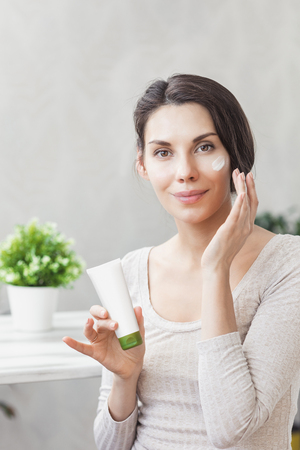 Girl applies face cream. Skin care and beauty concept. Young woman applying moisturizer on her face. Face Skin care. Applying Cream on her Face Reklamní fotografie