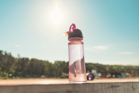 Sport and Fitness equipment. Water bottle, on wooden pier by the sea, at dawn.