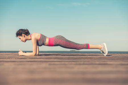 Sporty young girl in the morning on the pier on seashore, practicing yoga. Woman do gymnastics outdoors. Health and Yoga Concept. Female meditation for fitness lifestyle the nature background Reklamní fotografie