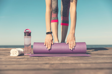 Sport and Fitness equipment. Sneakers, mat for fitness, water, on wooden pier by the sea, at dawn.