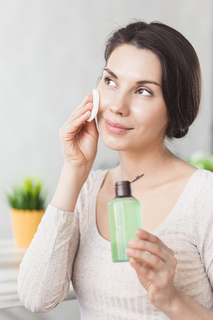 Makeup remove skin care. Closeup woman holding cotton swab and makeup remover liquid cosmetic in hands. Reklamní fotografie