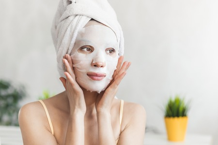 Cuidado de la piel facial. Atractiva mujer joven envuelta en una toalla de baño, con mascarilla hidratante blanca