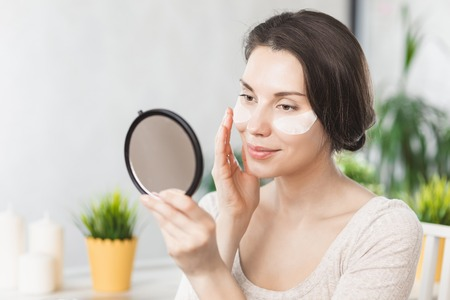 Portrait Of Beautiful Young Woman with Natural Makeup applying white Under Eye Patches Beauty Mask On Face. Reklamní fotografie