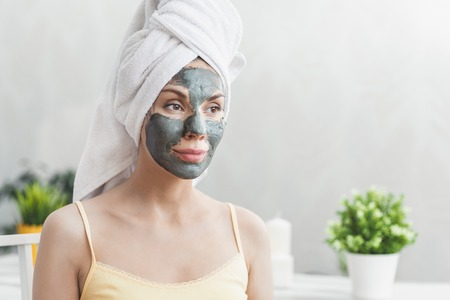 Face Skin care. Attractive Young Woman Wrapped in Bath Towel, applying clay mud mask to face.