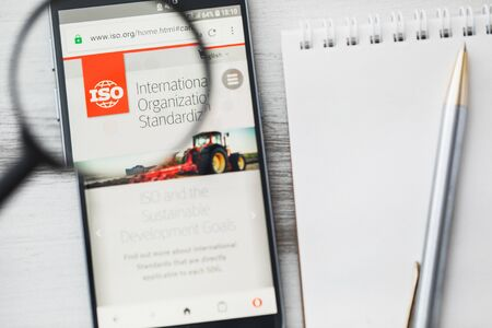 Los Angeles, California, USA - 3 April 2019: ISO International Organization for Standardization official website homepage under magnifying glass. Concept ISO logo visible on tablet screen, smartphone