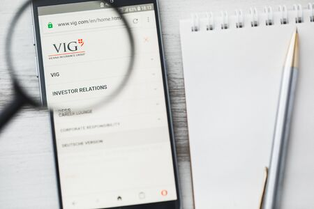 Los Angeles, California, USA - 3 April 2019: VIG Vienna Insurance Group Wiener Versicherung official website homepage under magnifying glass. Concept VIG logo visible on tablet screen, smartphone