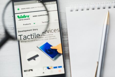 Los Angeles, California, USA - 3 April 2019: Nidec Corporation official website homepage under magnifying glass. Concept Nidec Electronic components logo visible on tablet screen, smartphone