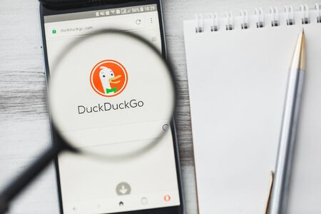 Los Angeles, California, USA - 9 June 2019: DuckDuckGo, Web search engine official website homepage under magnifying glass. Concept DuckDuckGo.com logo visible on smartphone, tablet screen