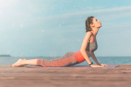 Sporty young girl in the morning on pier on seashore, practicing yoga. Woman do gymnastics outdoors. Health and Yoga Concept. Female lifestyle meditation for fitness lifestyle the nature background Stockfoto