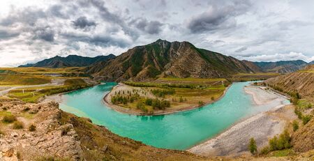 Panorama of mountain river on background of beautiful mountains in cloudy weather. View of turquoise river in the mountains on the background gloomy sky.
