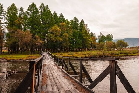 Old ruined wooden bridge over the river in the forest in cloudy weather. Wooden bridge washed away.
