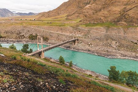Old ruined wooden bridge over the turquoise river in the mountains in cloudy weather.