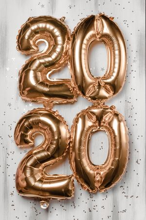 Happy New year 2020 celebration. Bright gold balloons figures, New Year Balloons with glitter stars on wood white background. Christmas and new year celebration. Gold foil balloons numeral 2020