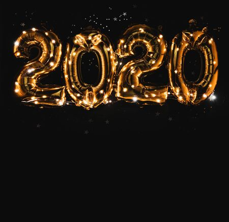 Happy New year 2020 celebration. Bright gold balloons figures, New Year Balloons with glitter stars on dark background. Christmas and new year celebration. Gold foil balloons numeral 2020 and confetti Stockfoto