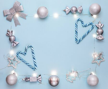 Happy New year 2020. Merry Christmas and Happy Holidays greeting card. Christmas composition. Silver decorations on pastel blue background. Winter, new year concept. Flat lay, top view, copy space