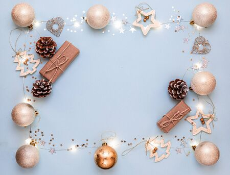 Happy New year 2020. Merry Christmas and Happy Holidays greeting card. Christmas composition. Gold decorations on pastel blue background. Winter, new year concept. Flat lay, top view, copy space