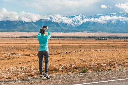 Young girl tourist, photographs on a smartphone, beautiful landscapes, mountains with snow-capped peaks.