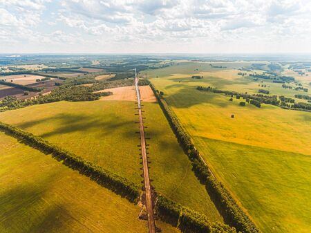 Aerial view on road under construction, among forests, fields and villages. Road works in the forest and in fields. Dirt road in an open area. Railroad construction through fields and meadows Stockfoto
