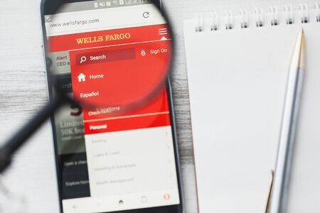 San Francisco, California - 15 January 2020: Wells Fargo official website homepage under magnifying glass. Concept Wells Fargo Bank logo visible on tablet screen, smartphone