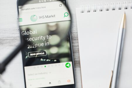 London, United Kingdom - 15 January 2020: IHS Markit official website homepage under magnifying glass. Concept IHS Markit Information services logo visible on smartphone, tablet screen