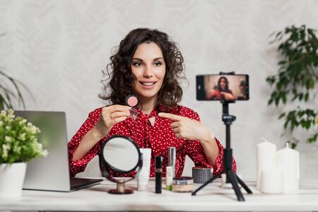Influencer Young girl blogger talks about makeup. Woman recording video blog tells how to be beautiful. Bloger talks facial beauty treatments. Vloggre broadcasts how to use of cosmetic Stock Photo