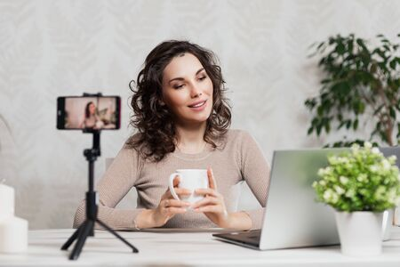 Influencer Young girl blogger talks about to your subscribers. Woman recording video blog tells be in social networks. Bloger talks facial how to organize your blog. Vloggre recording new broadcasts