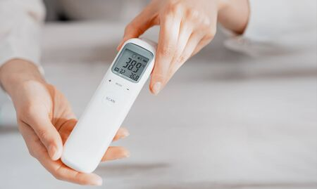 Female doctor in closeup shows thermometer with high temperature. Concept nCov 2019. Nurse demonstrates thermometer of coronavirus infected. High temperature electronic thermometer.