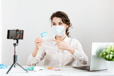 Influencer Girl blogger in medical mask talks about coronavirus. Woman recording video blog tells how to protect yourself from 2019-n ov. Bloger talks mers-cov how to use of alcohol wipes, thermometer