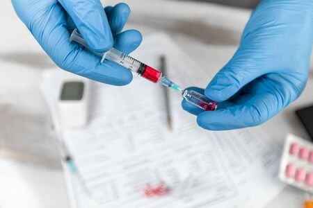 Doctor in rubber gloves is injecting vaccine into syringe. Hands closeup gloved in medical protects the filled syringe with medication. Concept Coronavirus nCov 2019. syringe with red solution. Stock Photo