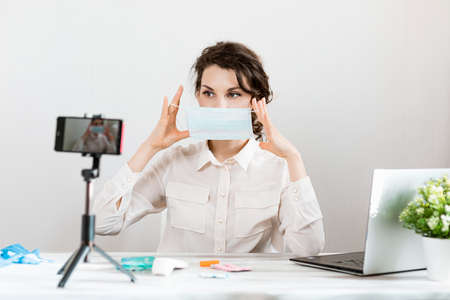 Influencer Girl blogger in medical mask talks about coronavirus. Woman recording video blog tells how to protect yourself from 2019-nCov. Bloger talks mers-cov how to use of alcohol wipes,thermometer
