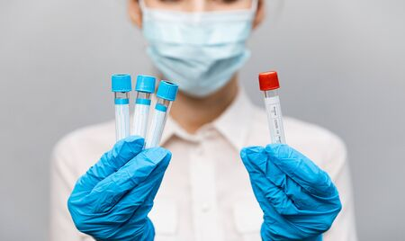 Girl Doctor in medical mask and rubber gloves, holds in her hands, closeup of test tube with tests for the presence of covid-19. Doctor in medical clothes demonstrates test tubes with coronavirus