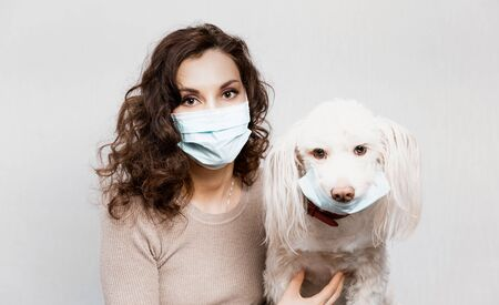 Woman in protective surgical mask holds dog pet in face mask. Coronavirus disease COVID-19 is dangerous for pets. Girl in medical mask and dog in protective mask. Coronavirus pandemic Precautions