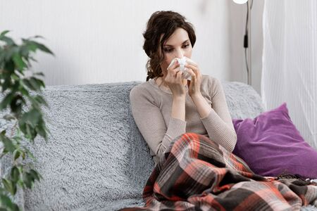 Sick woman suspected of covid-19, being at home in bed, measures the temperature and sneezes. Sick woman sitting under the blanket. Girl is quarantined with suspected coronavirus Stock Photo