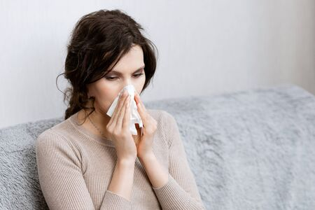 Sick woman suspected of covid-19 being at home in bed sneezes. Closeup sick girl sneezes in handkerchief Girl is quarantined with suspected coronavirus. Young woman sick in bed