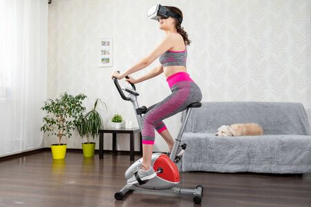 Young girl stay home in quarantine and go in for sports with virtual reality glasses. Woman exercise yoga while at home wearing virtual reality glasses