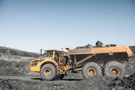 Large quarry dump truck. Loading the rock in dumper. Loading coal into body truck. Production useful minerals. Mining truck mining machinery, to transport coal from open-pit excavator work